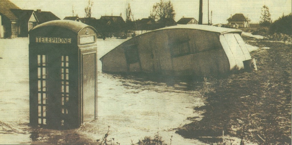 Misery - a telephone box, a caravan and houses, seen in the background, are submerged by flood water